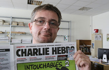 Publishing director of the satyric weekly Charlie Hebdo, Charb, displays the front page of the newspaper as he poses for photographers in Paris, Wednesday, Sept. 19, 2012. Police took up positions outside the Paris offices of the satirical French weekly that published crude caricatures of the Prophet Muhammad on Wednesday that ridicule the film and the furor surrounding it. The provocative weekly, Charlie Hebdo, was firebombed last year after it released a special edition that portrayed the Prophet Muhammad as a