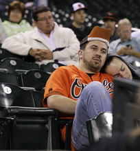 Tired fans wait out the ending of an 18-inning baseball game between the Baltimore Orioles and the Seattle Mariners in the early hours of Wednesday, Sept. 19, 2012, in Seattle. The Orioles beat the Mariners, 4-2. (AP Photo/Ted S. Warren)