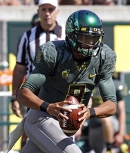 Oregon quarterback Marcus Mariota looks for a receiver as he scrambles out of the pocket during the first half of their NCAA college football game against Tennessee Tech in Eugene, Ore., Saturday, Sept. 15, 2012. Mariota threw for 308 yards and four touchdowns before No. 4 Oregon won 63-14. (AP Photo/Don Ryan)