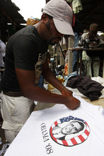 In this photo taken Monday, June. 18, 2012. An unidentified man looks at T-Shirt with a portrait of U.S President, Barrack Obama, at the secondhand clothes market in Lagos, Nigeria. Shipping container after shipping container arrives to this market in Lagos, Nigeria's largest city, filled to the brim with plastic-wrapped bales of secondhand clothes from the U.S. and elsewhere in the world. Traders scour, barter, hem and haw over T-shirts, bras, pants and shoes sent to help clothe a nation of more than 160 million people where the textile industry largely collapsed years ago.  (AP Photo/Sunday Alamba)