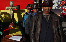 State miners stand by the coffin containing the remains of fellow miner Hector Choque as they hold a vigil in La Paz, Bolivia, Wednesday, Sept. 19, 2012. Choque died when he was injured during violent clashes that erupted Tuesday when one faction of privately contracted miners threw a small dynamite charge into a crowd of state miners who were protesting on a main road in the Bolivian capital. The two sides have been staging rival protests for months for control of the Colquiri tin mine, south of La Paz. (AP Photo/Juan Karita)