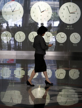 An Indonesian woman walks past clocks showing world time at the Jakarta Stock Exchange in Jakarta, Indonesia, Wednesday, Sept. 19, 2012. (AP Photo/Achmad Ibrahim)