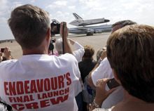 Scott Rush, left, photographs space shuttle Endeavour atop the shuttle aircraft carrier after landing Wednesday, Sept. 19, 2012, at Ellington Field in Houston. Endeavour is making a final trek across the country to the California Science Center in Los Angeles, where it will be permanently displayed. (AP Photo/David J. Phillip