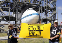 Kennedy Space Center employees, Bonnie and Jim Ekey pose for friends wearing Pittsburg Steeler NFL football gear in front of space shuttle Endeavour atop a modified jumbo jet in the mate/demate structure at the Kennedy Space Center,  Tuesday, Sept. 18, 2012, in Cape Canaveral, Fla. Jim Ekey grew up in the Pittsburgh area and remains a Steeler fan. (AP Photo/Terry Renna)