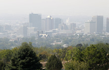 Al Hartmann  |  The Salt Lake Tribune Downtown Salt Lake City skyline is obscured by smoke seen from a vantage point at 11th Avenue Park just a  couple miles to the north Tuesday afternoon. Low visibility and haze is smoke from wildfires in Idaho drifting down into the state.  It was a red air day along the Wasatch front.