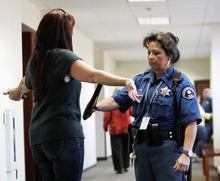 Sheriff's deputy Donelle Wells wands a family member as she arrives for a hearing for suspected theater shooter James Holmes in district court in Centennial, Colo., on Thursday, Sept. 20, 2012.  Holmes has been charged in the shooting at the Aurora theater on July 20 that killed twelve people and injured more than 50. (AP Photo/Ed Andrieski)