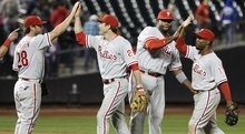 Philadelphia Phillies' Kevin Frandsen (28) celebrates with teammates Chase Utley (26), Ryan Howard, second from right, and Jimmy Rollins (11) after a baseball game against the New York Mets, Wednesday, Sept. 19, 2012, in New York. Howard hit a two-run home run in the ninth inning as the Phillies won the game 3-2. (AP Photo/Frank Franklin II)