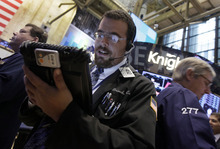 FILE-In this Friday Sept. 7, 2012, file photo, trader Richard Scardino, center, works on the floor of the New York Stock Exchange. Stocks edged higher during trading on Wednesday, Sept. 12, 2012. Investors were happy to see that Germany's highest court cleared the way for that country to participate in a European rescue fund. Attentions now shift to the Federal Reserve, which wraps up its two-day meeting Thursday. (AP Photo/Richard Drew, File)