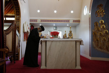 Rev. Joseph Boules, left, prays during a mass at St. Mary and St. Verena Orthodox Coptic Church in Anaheim, Calif., Wednesday, Sept. 19, 2012. (AP Photo/Jae C. Hong)