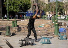 An Egyptian riot policeman smashes plastic chairs as police clear Tahrir Square in Cairo, Egypt, Saturday, Sept. 15, 2012 after days of protests near the U.S. embassy over a film insulting Prophet Muhammad. (AP Photo/Mohammed Asad)