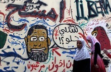 Egyptian women walk past a newly painted mural with a caricature depicting Egyptian president Mohammed Morsi on a newly whitewashed wall in Tahrir Square, Cairo, Egypt, Thursday, Sept. 20, 2012. Under cover of darkness, a few municipality workers quietly began to paint over an icon of Egypt's revolution: a giant, elaborate public mural on the street that saw some of the most violent clashes between protesters and police over the past two years. Arabic reads
