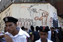 Two Egyptian policemen guard while Egyptian men gather by an artist working on a mural with faces depicting ousted Egyptian president Hosni Mubarak, on a newly whitewashed wall in Tahrir Square, Cairo, Egypt, Thursday, Sept. 20, 2012. Under cover of darkness, a few municipality workers quietly began to paint over an icon of Egypt's revolution: a giant, elaborate public mural on the street that saw some of the most violent clashes between protesters and police over the past two years. Arabic reads