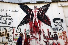 Two Egyptian youths walk past a newly painted mural on a newly whitewashed wall in Tahrir Square, Cairo, Egypt, Thursday, Sept. 20, 2012. Under cover of darkness, a few municipality workers quietly began to paint over an icon of Egypt's revolution: a giant, elaborate public mural on the street that saw some of the most violent clashes between protesters and police over the past two years. Arabic reads