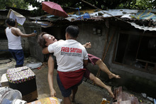 An informal settler is carried by her husband as a demolition crew, unseen, tears down their shanty in Taguig city Thursday, Sept. 20, 2012, east of Manila, Philippines. The informal settlers' community of mostly retired police and military personnel was demolished to pave the way for new development projects.  (AP Photo/Bullit Marquez)