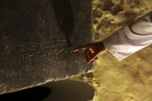Mohammed Abd al-Sitar, 28, an archaeologist with the Egyptian Supreme Council of Antiquities points out a hieroglyph on a sarcophagus during the re-opening of the