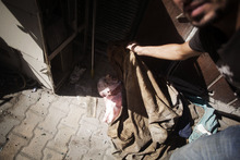 In this Wednesday, Sept. 19, 2012 photo,the body of an elderly man, said by rebels to be a Coptic Christian, lies at the door of a hospital controlled by the Free Syrian Army in Aleppo, Syria.(AP Photo/Manu Brabo)