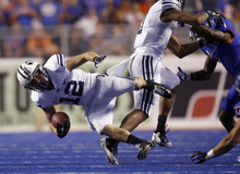 JD Falslev #12 of the BYU Cougars is tripped up in the first half against Boise State at Bronco Stadium on Thursday September 20, 2012.