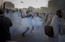A Pakistani protestor hurls back a tear gas canister fired by police during clashes that erupted as the demonstrators tried to approach the U.S. embassy in Islamabad, Pakistan, Friday, Sept. 21, 2012. Over a dozen people were killed as tens of thousands protested against the film around the country after the government encouraged peaceful protests and declared a national holiday —