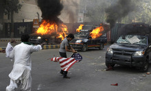 A protester carries a representation of a U.S. flag as police vehicles burn in Karachi, Pakistan on Friday, Sept 21, 2012. Tens of thousands protested against the film around the country after the government encouraged peaceful protests and declared a national holiday —