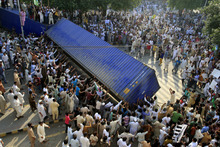 Pakistani protesters topple a shipping container police used to block the road to the US consulate in Lahore, Pakistan on  Friday, Sept 21, 2012. Tens of thousands protested around the country against an amateurish anti-Muslim film produced in the United States and vulgar caricatures of the Prophet Muhammad published in a French satirical weekly after the government encouraged peaceful protests and declared a national holiday —