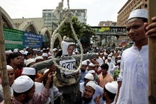 Bangladeshi Muslims hold up an effigy representing U.S. President Barack Obama to the hangman's noose during a protest against anti-Islam film produced in the United States in Dhaka, Bangladesh, Friday, Sept. 21, 2012. The protest was against the film named