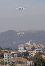 The Space Shuttle Endeavour mounted on NASA's Shuttle Carrier Aircraft,  passes over the Hollywood sign in Los Angeles, Friday, Sept. 21, 2012.  Endeavour is making a final trek across the country to the California Science Center in Los Angeles, where it will be permanently displayed. (AP Photo/John Hopper)