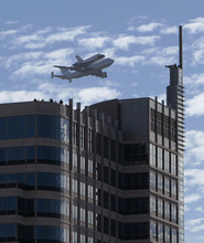 The space shuttle Endeavour flys low over the Esquire Building in Sacramento, Calif.  Friday, Sept. 21, 2012,  Endeavour is making a final trek across the country to the California Science Center in Los Angeles, where it will be permanently displayed.(AP Photo/Rich Pedroncelli)