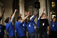 Apple workers gesture with five figners at customers leaving their store after purchasing iPhone 5 handsets in Covent Garden, London, Friday, Sept. 21, 2012. In a now familiar global ritual, Apple fans jammed shops Friday to pick up the tech juggernaut's latest iPhone.  The smartphone is being launched in the U.S., Britain, Canada, France and Germany. It will go on sale in 22 more countries a week later. (AP Photo/Matt Dunham)
