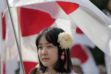 A woman holds a Japanese national flag as she takes part in a rally, opposing China's territorial claim over the disputed islands, called Senkaku in Japan and Diaoyu in China, at a park in Tokyo, Saturday, Sept. 22, 2012. (AP Photo/Itsuo Inouye)