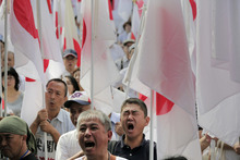 Protesters holding Japanese national flags shout slogans during a rally, opposing China's territorial claim over the disputed islands, called Senkaku in Japan and Diaoyu in China, at a park in Tokyo, Saturday, Sept. 22, 2012. (AP Photo/Itsuo Inouye)