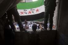 In this Friday, Sept. 21, 2012 photo,  Free Syrian Army rebels hold a revolutionary flag on it during a demonstration in the Bustan al-Qasr neighborhood of Aleppo, Syria. The Britain-based Syrian Observatory for Human Rights said Friday that nearly 30,000 Syrians have been killed during the 18-month uprising against the Assad regime. Arabic on flag is reversed, but reads,