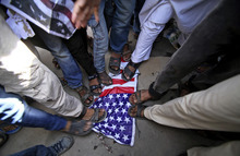 Indian Muslims stamp on a U.S. flag during a protest rally against an anti-Islam film called
