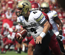 Colorado quarterback Jordan Webb (4) scrambles to avoid the rush of Washington State linebacker Darryl Monroe, obscured, during the first quarter of an NCAA college football game Saturday, Sept. 22, 2012, at Martin Stadium in Pullman, Wash. (AP Photo/Dean Hare)