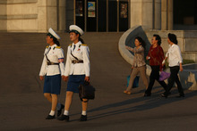 In this photo taken Saturday, Sept. 22, 2012, two North Korean traffic coordinators holding hands walk on a street in Pyongyang, North Korea. (AP Photo/Vincent Yu)