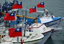 A fisherman raises a Taiwanese national flag as several dozen fishing boats set out from the Suao harbor, northeastern Taiwan, to the disputed islands in the East China Sea, Monday, Sept. 24, 2012. The islands, called Senkaku in Japan and Diaoyu in China, are controlled by Japan but also claimed by China and Taiwan, and have been a key part of simmering regional tensions over rival territorial claims. (AP Photo/Wally Santana)