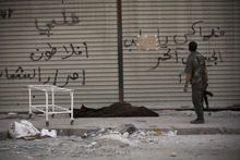 In this Saturday Sept. 22, 2012 photo, a Free Syrian Army soldier stands next to a dead body in front of Dar el-Shifa hospital in Aleppo, Syria. Partial translation in Arabic reads,