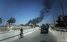 In this Sunday, Sept. 23, 2012 photo, black smoke leaps the air from government shelling in a residential area in Aleppo, Syria. (AP Photo/ Manu Brabo)