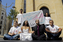 Lebanese activists, dressed as a bride and groom, center, protest with others as they take part in a campaign promoting the legalization of civil marriage in Lebanon in front of the Parliament in downtown Beirut, Lebanon, Monday, Sept. 24, 2012. The banner in Arabic reads,