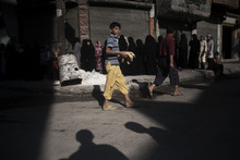 In this Saturday, Sept. 22, 2012 photo, a Syrian boy carries loaves of bread while women stand in line to buy bread outside of a bakery in the Saif al Dula neighborhood of Aleppo, Syria, Friday, Sept. 21, 2012. (AP Photo/ Manu Brabo)
