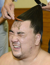 Mongolian sumo wrestler Harumafuji has his hair fixed after he beat compatriot and grand champion Hakuho in Tokyo on Sunday, Sept. 23, 2012.  Harumafuji won the Autumn Grand Sumo Tournament on Sunday and moved a step closer to promotion to the sport's highest rank. (AP Photo/Kyodo News) JAPAN OUT, MANDATORY CREDIT, NO LICENSING IN CHINA, HONG KONG, JAPAN, SOUTH KOREA AND FRANCE