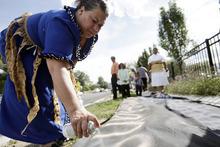Ashley Detrick  |  The Salt Lake Tribune Saane Lotaki spray paints a sign that says