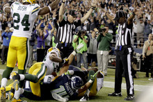 Officials signal a touchdown by Seattle Seahawks wide receiver Golden Tate, obscured, on the last play of an NFL football game against the Green Bay Packers, Monday, Sept. 24, 2012, in Seattle. The Seahawks won 14-12. (AP Photo/Stephen Brashear)