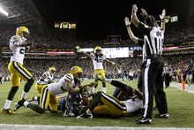 Officials signal after Seattle Seahawks wide receiver Golden Tate pulled in a last-second pass from quarterback Russell Wilson to defeat the Green Bay Packers 14-12 in an NFL football game, Monday, Sept. 24, 2012, in Seattle. The touchdown call stood after review. (AP Photo/The Seattle Times, John Lok)