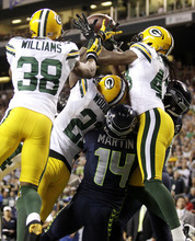 Green Bay Packers cornerbacks Tramon Williams (38) and Charles Woodson (21) and safety M.D. Jennings (43) fight for possession of a jump ball with Seattle Seahawks wide receivers Charly Martin (14) and Golden Tate, right, in the final seconds of the fourth quarter of an NFL football game, Monday, Sept. 24, 2012, in Seattle. Tate was ruled to have come down with the ball for a touchdown, and the Seahawks won 14-12. (AP Photo/Stephen Brashear)