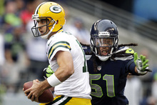 Green Bay Packers quarterback Aaron Rodgers, left, is sacked by Seattle Seahawks defensive end Bruce Irvin in the first half of an NFL football game, Monday, Sept. 24, 2012, in Seattle. (AP Photo/Stephen Brashear)