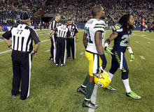 Officials discuss the final play of the game as Green Bay Packers' Charles Woodson, second from right, and Seattle Seahawks' Earl Thomas, right, leave the field in the second half of an NFL football game, Monday, Sept. 24, 2012, in Seattle. The final play was ruled a Seattle touchdown as the Seahawks defeated the Packers 14-12. (AP Photo/Ted S. Warren)