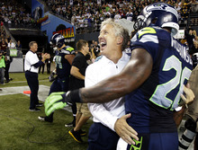 Seattle Seahawks head coach Pete Carroll, second from right, celebrates with Seahawks' Michael Robinson after defeating the Green Bay Packers 14-12 an NFL football game, Monday, Sept. 24, 2012, in Seattle. (AP Photo/Ted S. Warren)