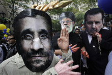 Men wearing masks of Iranian President Mahmoud Ahmadinejad, left, Iranian Ayatollah Ali Khamenei, center, and Syrian President Bashar al-Assad, right, participate in a protest led by Iranian Americans and Syrian Americans outside the United Nations, Wednesday, Sept. 26, 2012 in New York. (AP Photo/Mark Lennihan)