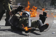 A riot policeman reacts after he was hit by a petrol bomb thrown by protesters during a nationwide general strike in Athens, Wednesday, Sept. 26, 2012. Police clashed with protesters hurling petrol bombs and bottles in central Athens Wednesday after an anti-government rally called as part of a general strike in Greece turned violent.  (AP Photo/Petros Giannakouris)