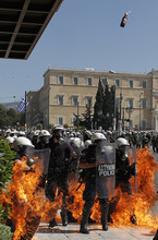 A fire bomb explodes among riot police during clashes in Athens Wednesday Sept. 26, 2012. Greek workers walked off the job Wednesday for the first general strike since the country's coalition government was formed in June, as the prime minister and finance minister hammered out a package of euros 11.5 billion ($14.87 billion) in spending cuts. Athens has struggled to come up with more punishing austerity measures that would be acceptable to its rescue creditors, with disagreements arising between the three parties that make up the coalition government. Greece's creditors have demanded more fiscal reforms if they are to continue handing out rescue loans preventing the country from a messy default that could roil the euro. (AP Photo/Nikolas Giakoumidis)